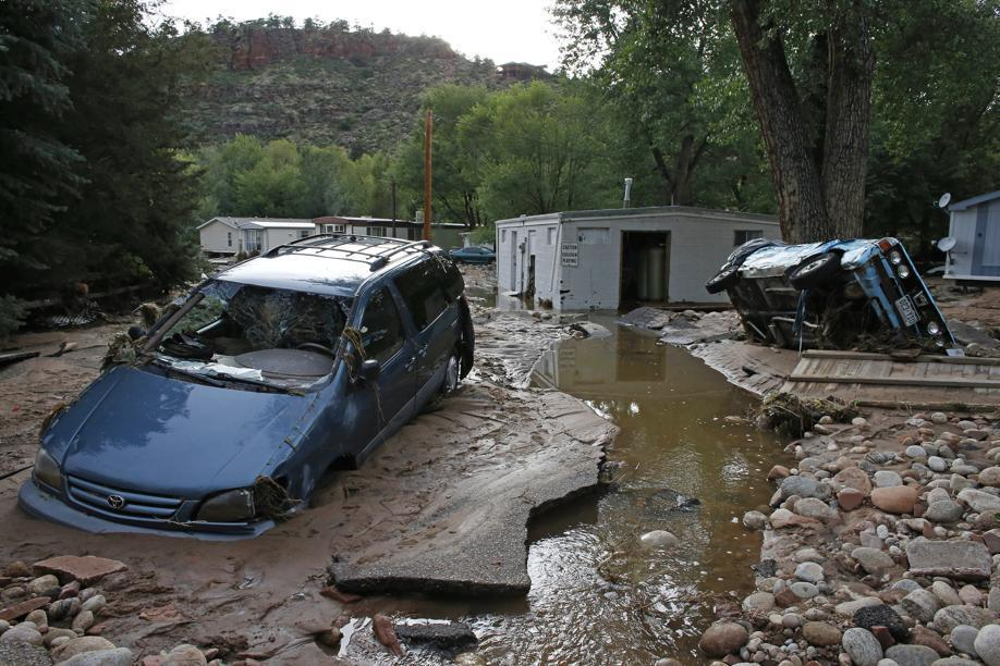 Cars lay mired in mud deposited by floods in Lyons, Colo., on Friday.
